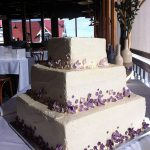 purple icing flowers on wedding cake