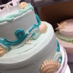 cake decorated with beach chairs waves and shells