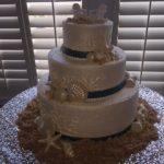cake decorated with two beach chairs on top and sand and sea shells