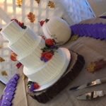 4 tiered white cake next to white pumpkin