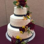 three tiered white cake with red and yellow flowers