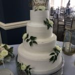 White 4 tiered cake with white roses and green leaves